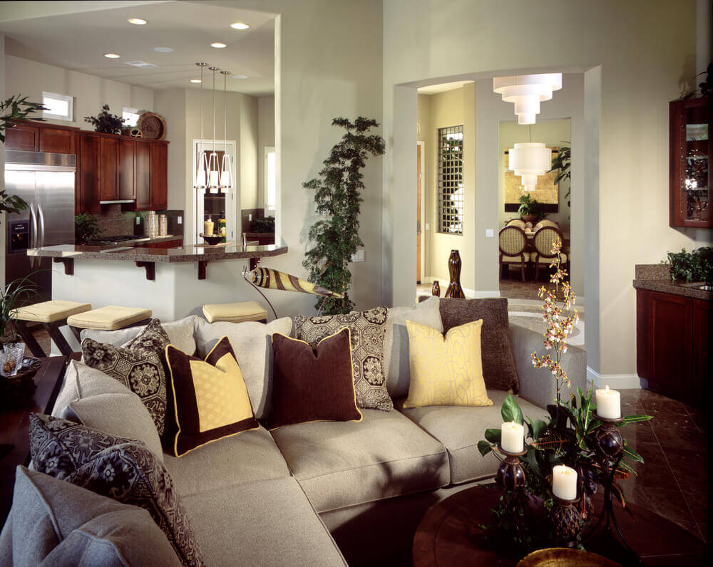 This cozy but open living room space holds contemporary grey L-shaped sectional with decorative pillows over dark brown marble flooring with nearly matching dark wood toned furniture and cabinetry.