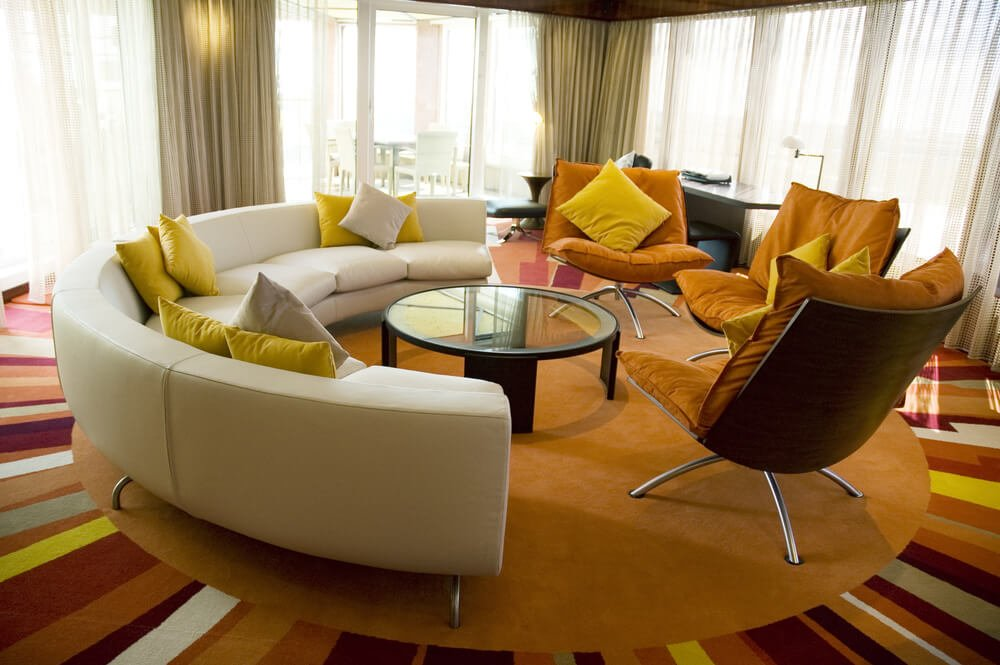 Circular living room features bright multi-colored sun-pattern carpeting, with semi-circular midcentury sectional on left, paired with plush orange cushion chairs on right. Round glass coffee table resides at center of this sunlit space.