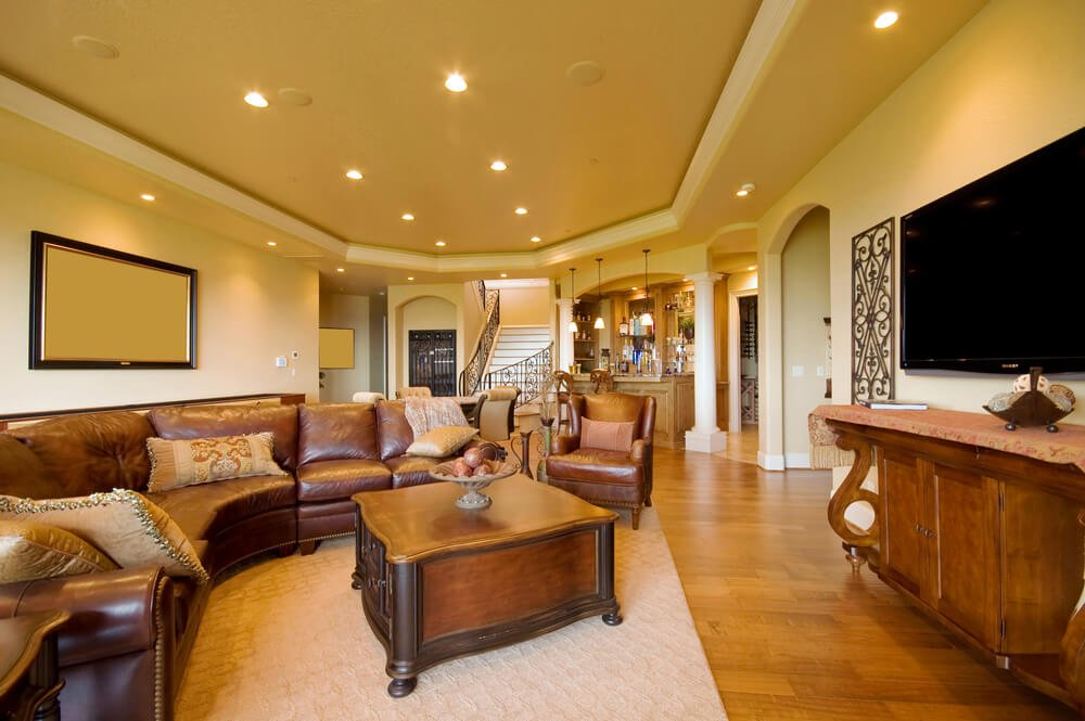 Wide open living room space holds semi-circular plush leather sectional sofa with large ornate coffee table on white rug. Natural hardwood flooring throughout unifies the space.