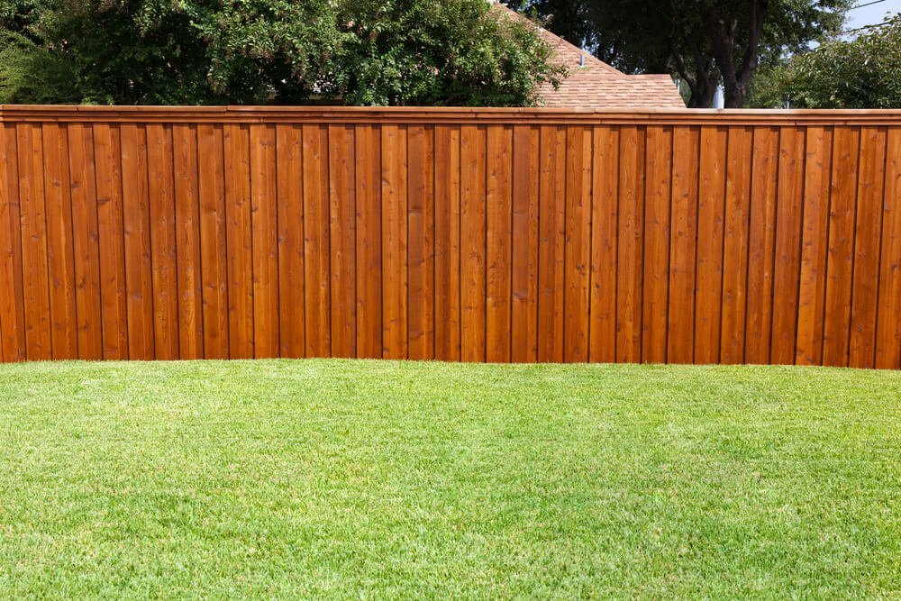 Here's another rich, warm toned wooden privacy fence with layered slats and horizontal top panel.