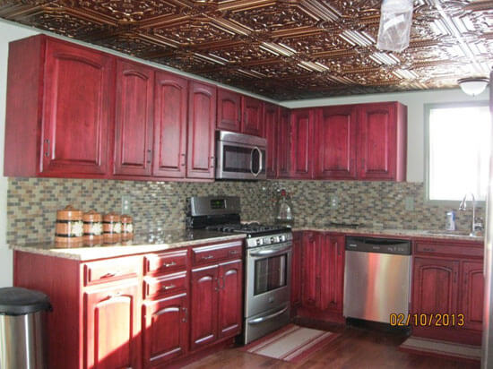 small red wood kitchen with faux tin ceiling tiles