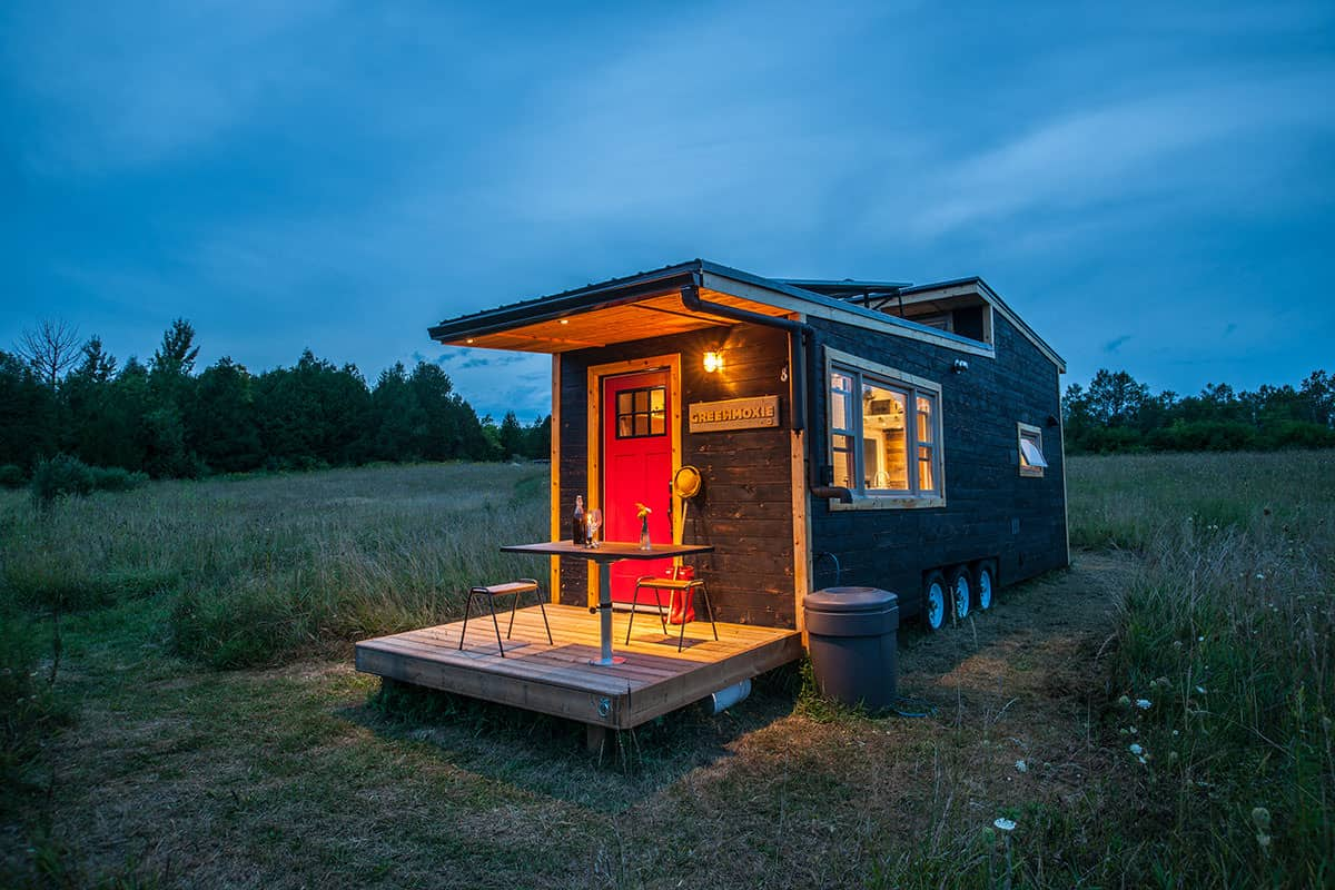 Fabulous tiny house on wheels with red door on the end that leads out to a deck which can fold up when traveling.