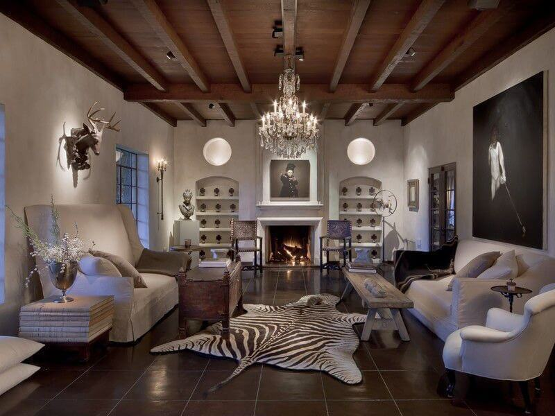 Large living room with dark brown tile floor on which a large zebra skin is placed as the central floor decor in between a high-back sofa, wood bench, regular-backed sofa, and reading chair.