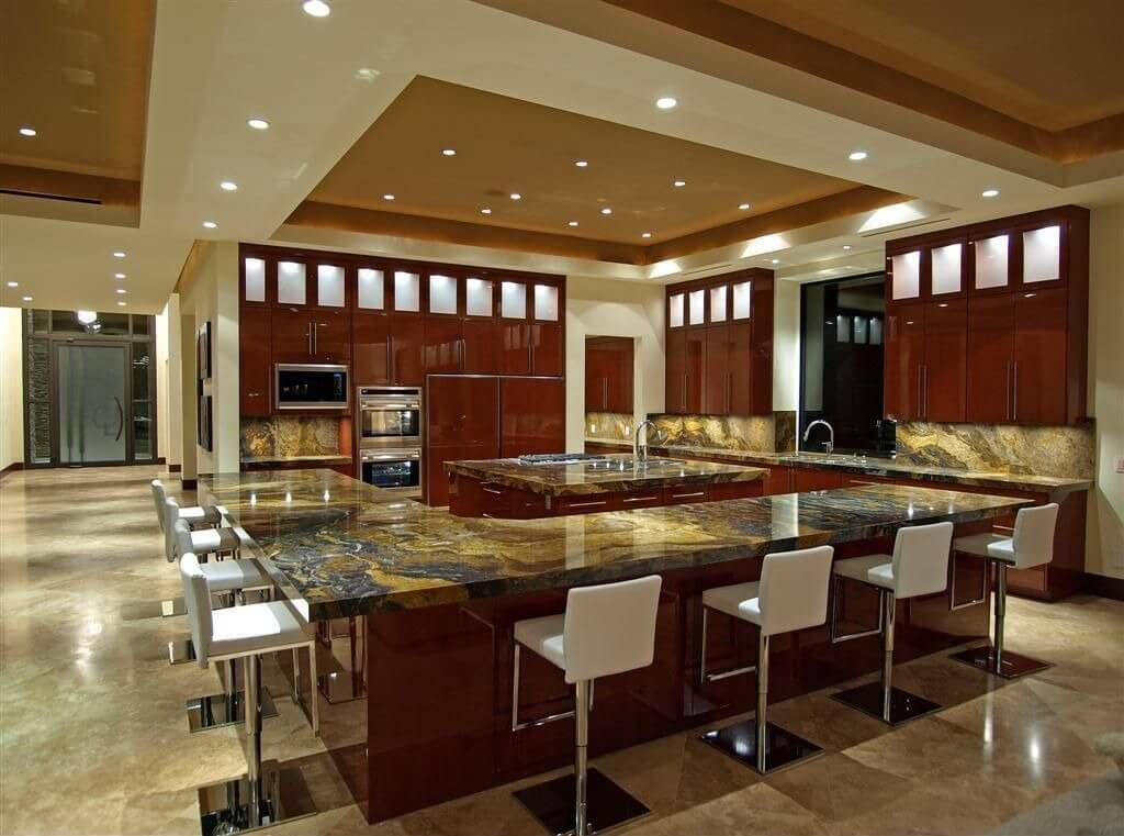 The kitchen is situated in a large open concept living area. The entire outer counter is an L-shaped diner counter with modern stools wrapping around the space.