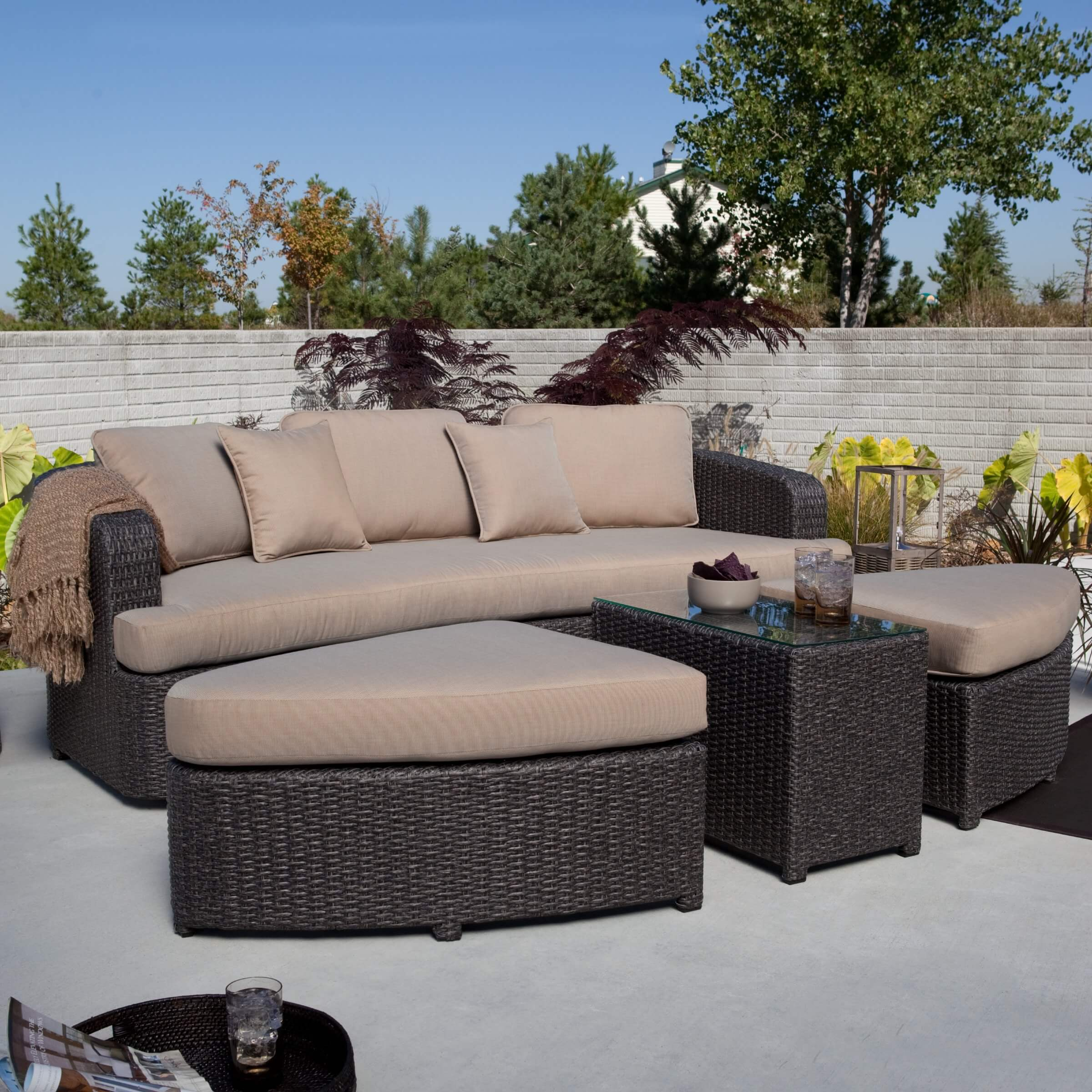 This patio sectional can transform from a conversation oriented set to a comfortable single piece lounger, offering configurations not found with most sets. Glass topped table section sits at center.