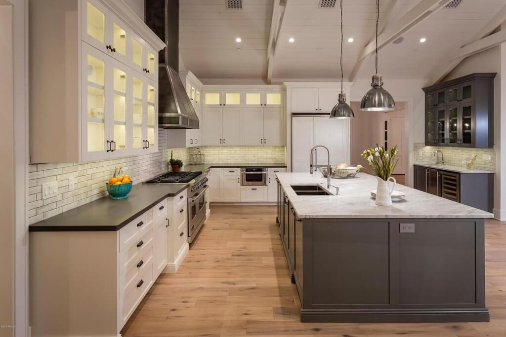 Large modern kitchen design with white and grey color scheme. The huge center space includes a massive island that provides the lion's share of the counter space. The cool grey tone is offset by the warm natural wood flooring.