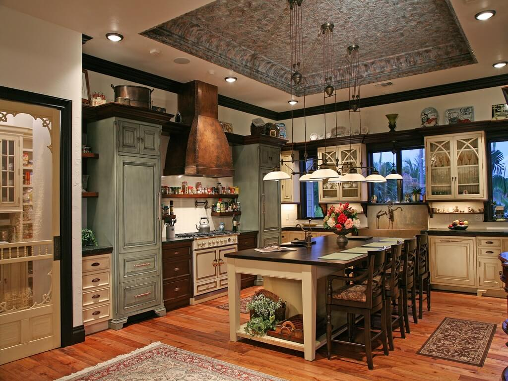 Luxury country kitchen. Multiple tones are used throughout the custom cabinetry - green, cream and dark wood. The honey-toned wood flooring adds to the multi-tone color motif.
