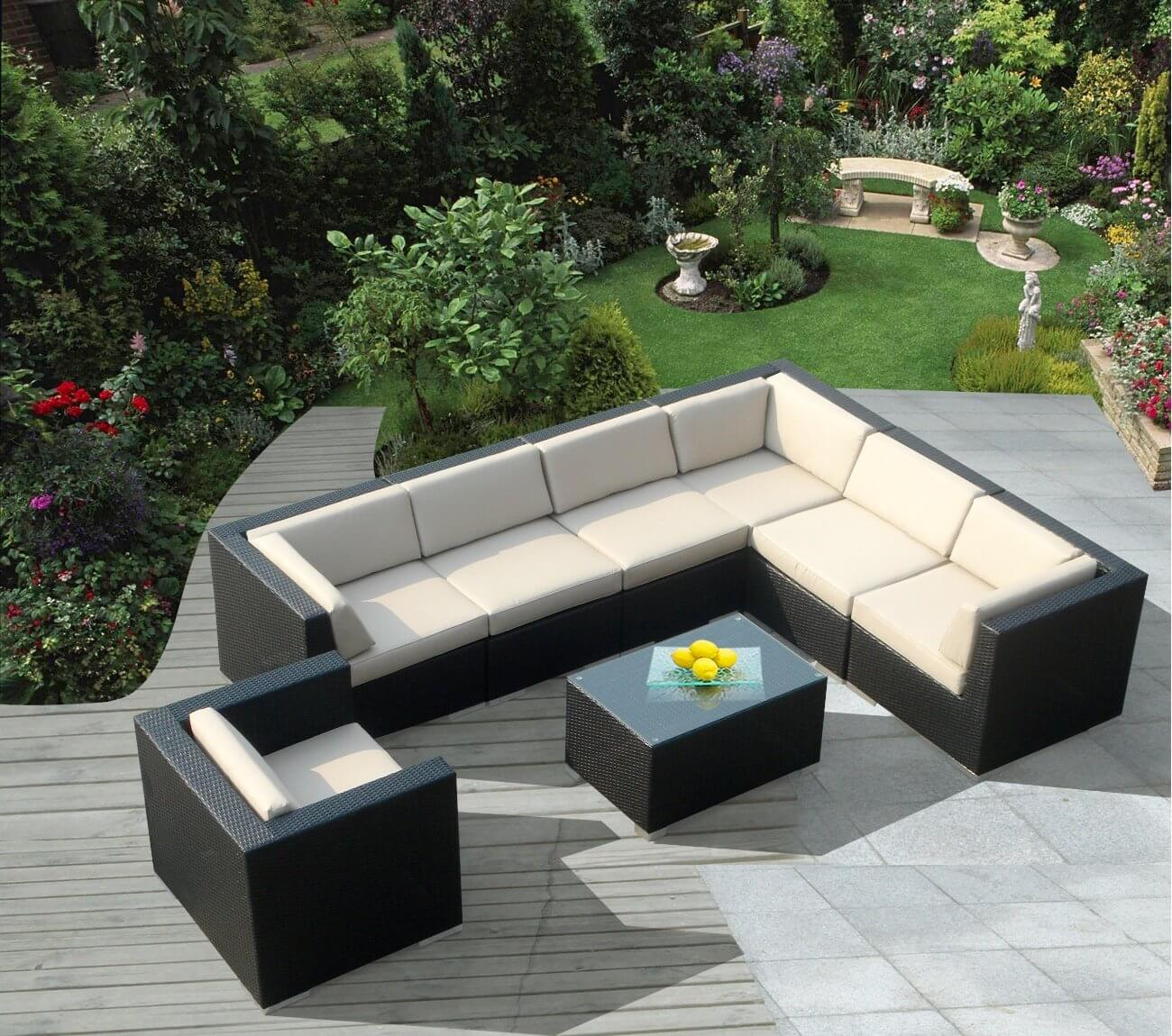 Lengthy L-shaped wicker patio sectional in black and eggshell tones features matching armchair plus glass-topped table for true conversational style.