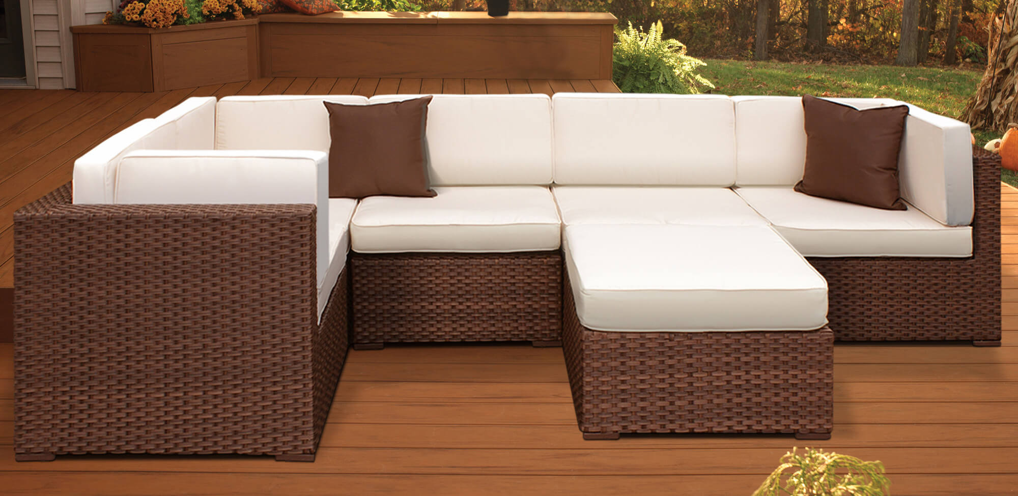 Brightly contrasting wicker patio sectional features white thick padded cushioning over chocolate body, with single ottoman section providing chaise functionality.