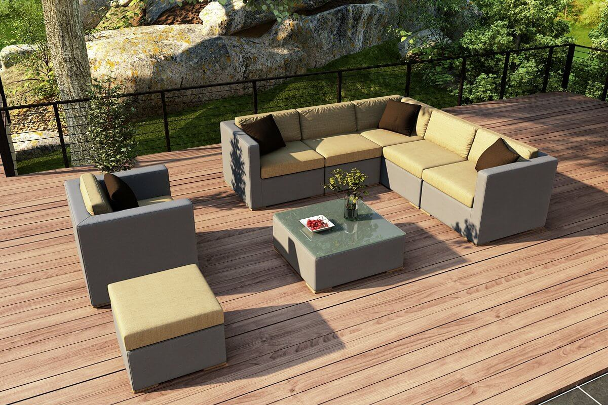 Ultra modern patio sectional features unique pairing of yellow and grey fabric surfaces, with ottoman section, armchair, and glass topped table at center.