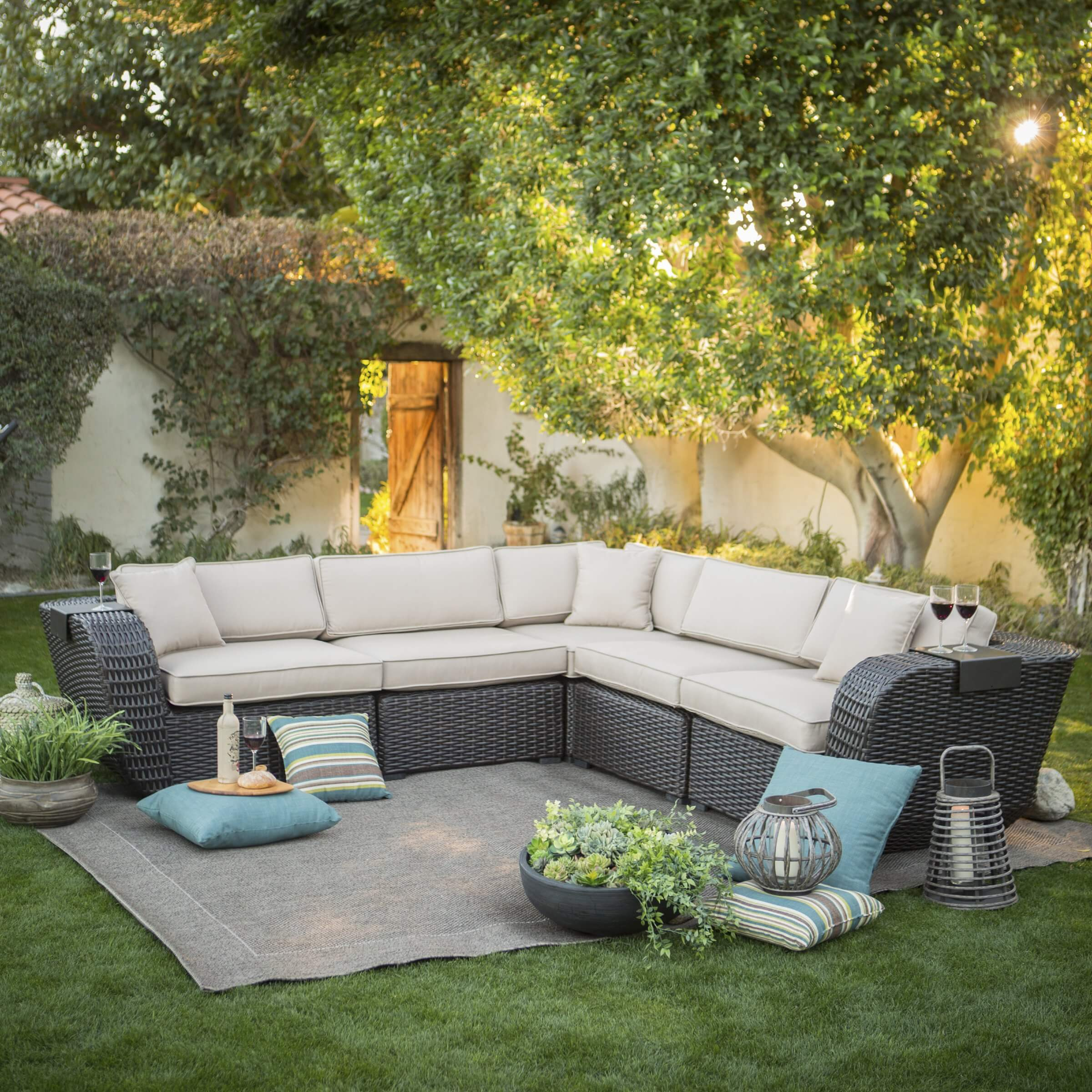 Large, plush L-shaped sectional features multiple detachable segments, thick resin wicker construction, an array of light toned cushioning, and small armrest attachments for drink surfaces.