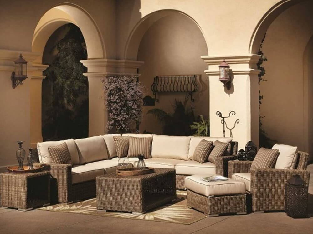 Lush, elaborate patio sectional features an array of configurable pieces, including main L-shaped sofa body, armchair, cushion topped ottoman, plus hollow storage coffee and end tables.