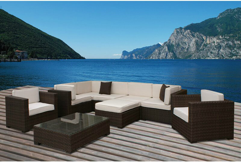 This sprawling patio sectional features a pair of armchairs in addition to the main sectional body, with ottoman and large glass surface table included.