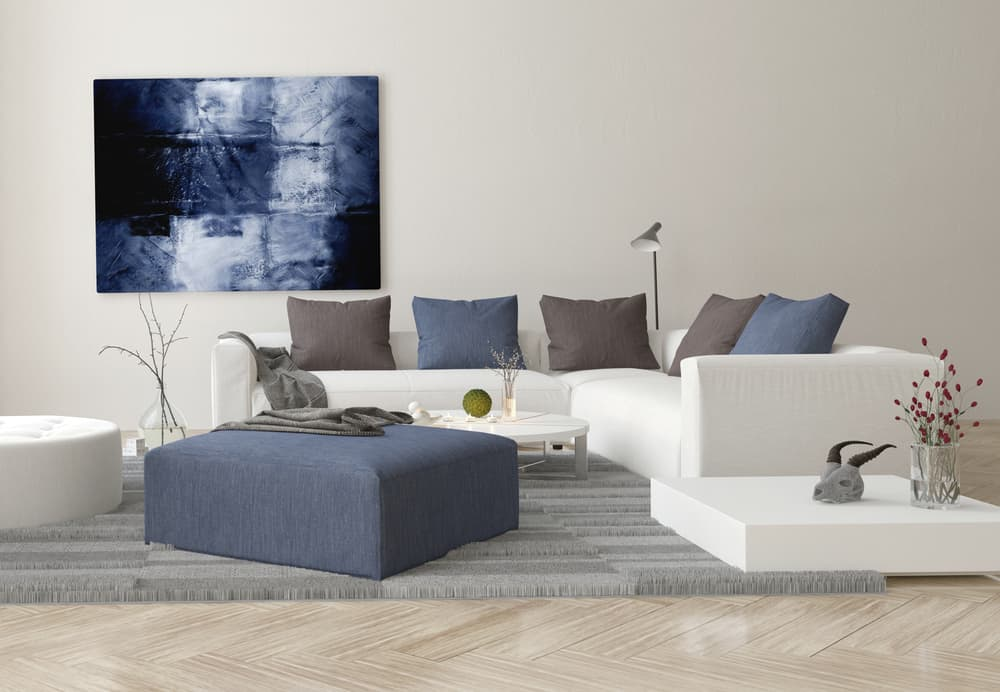 A casual color palette that includes a cream colored couch, blue and brown pillows, and a blue ottoman coffee table.