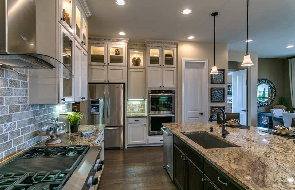 Luxury kitchen in L-shape with white cabinets and dark island.
