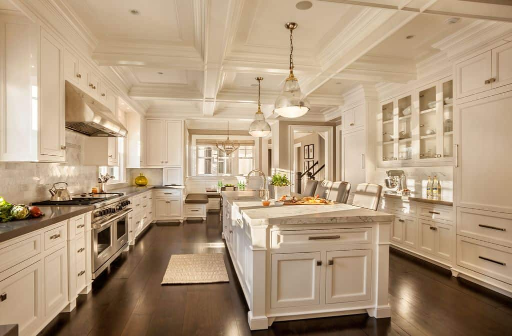 Massive white kitchen with ornate coffered ceiling in galley layout with large center island featuring a smooth marble countertop. There's a breakfast bar for four set on a hardwood flooring while being lighted by elegant pendant lights.