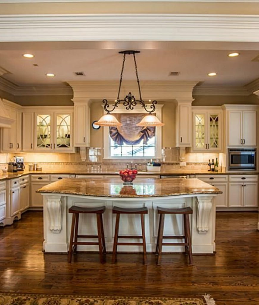 White traditional luxury kitchen with rich wood flooring in u-shape with center island.