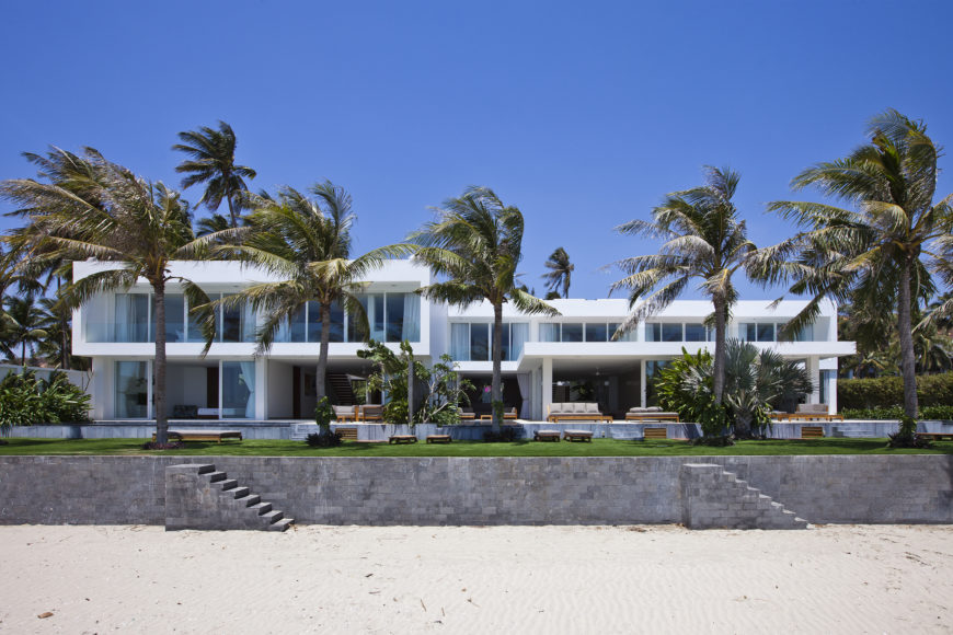 From the beach we see the raised construction wall protecting the home and surrounding lawn from the elements and erosion. Every exterior wall on this facade is floor to ceiling glass.