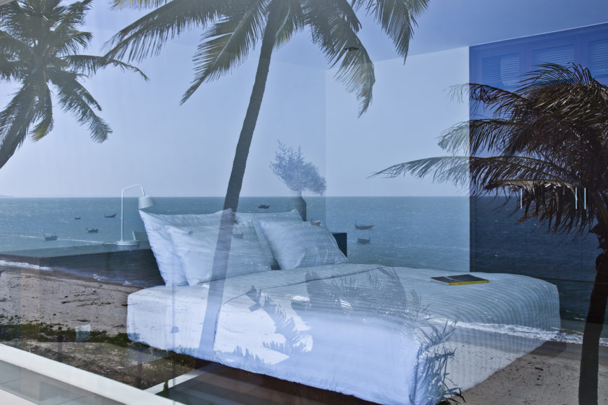 From outside, the cool glass reflects the ocean view guests enjoy from both inside and outside the home.