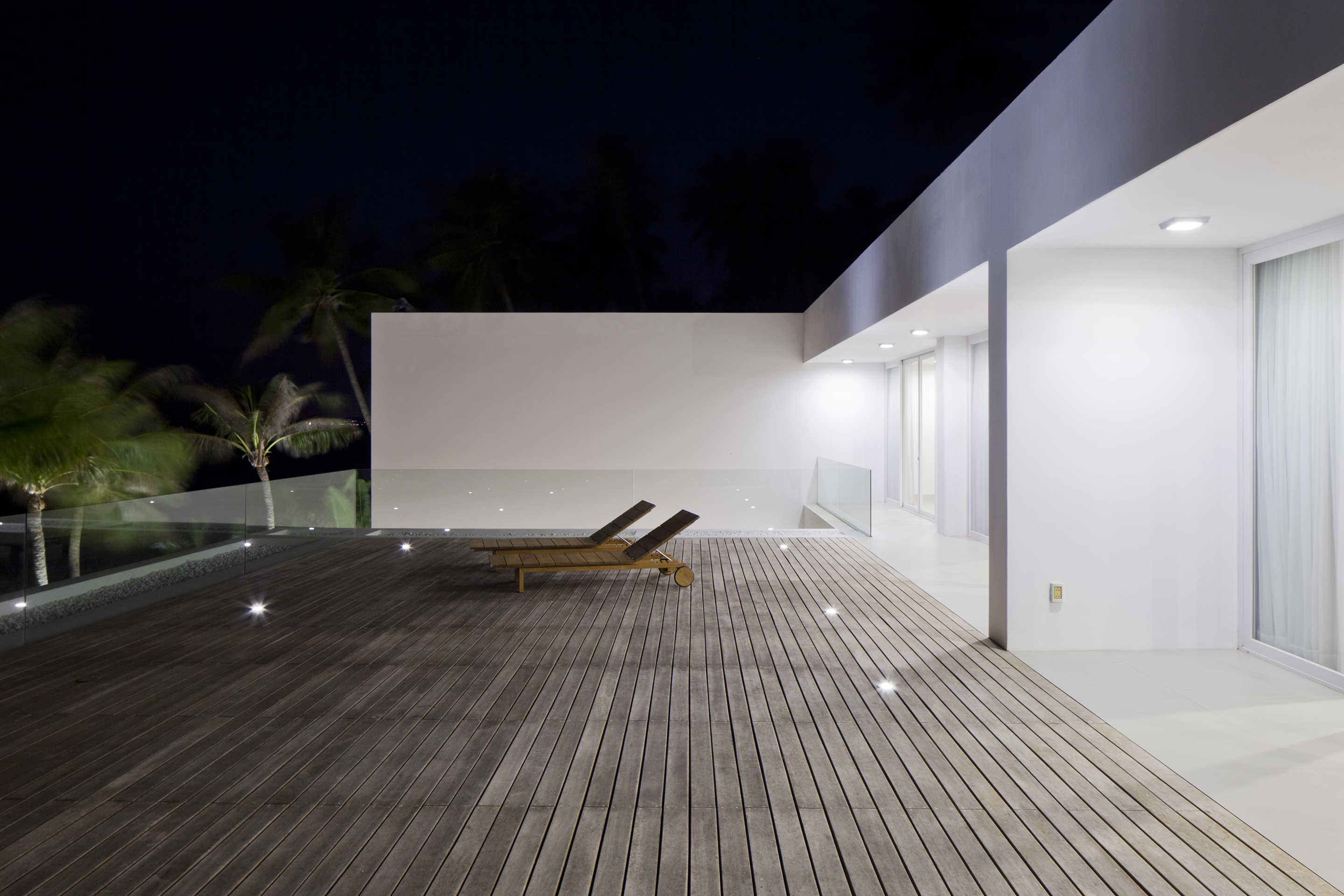 The upper level hardwood deck as seen at night, with embedded lighting in the floor and glass railings for transparent ocean views.