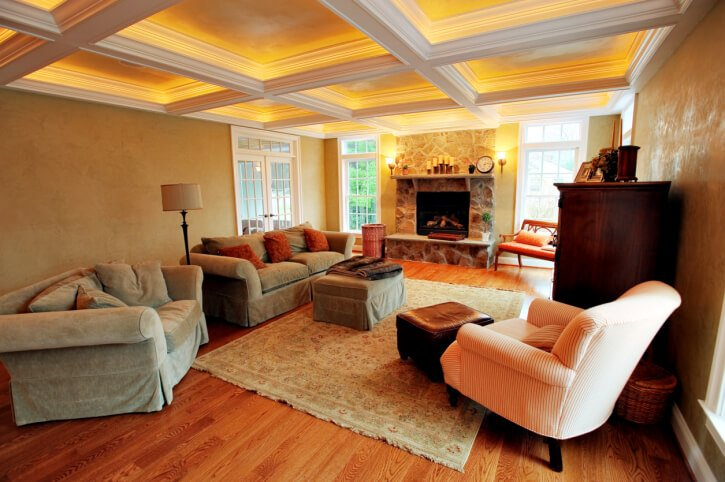 This cozy, warm toned living room features rich hardwood flooring, stone fireplace flanked by ceiling height windows, and interior-lit white ceiling beam detail.