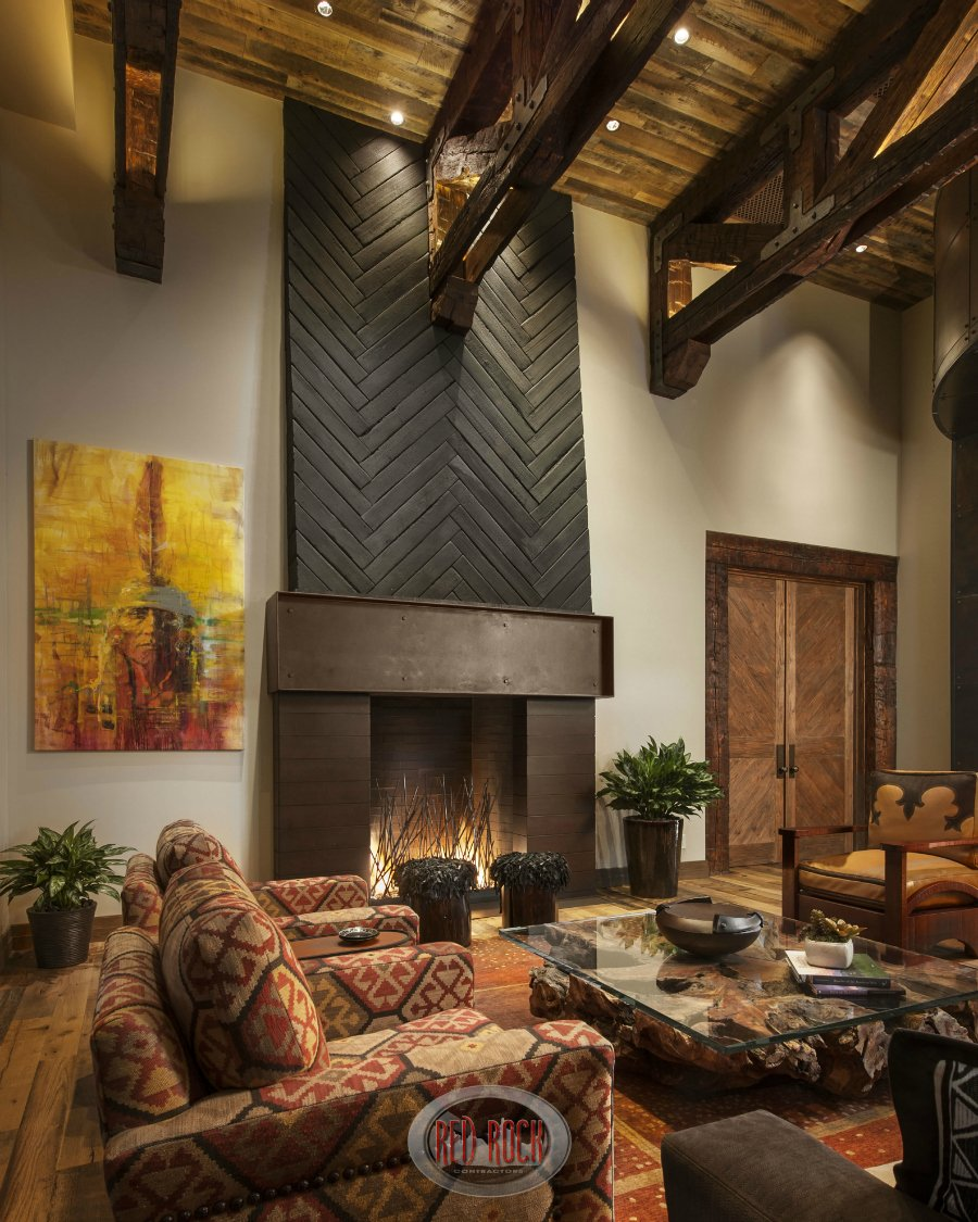 Soaring ceiling with exposed wood beams cap this rustic living room with a distressed wood floor, large modern fireplace, glass coffee table on a large wood stump all on top of a spacious area rug.