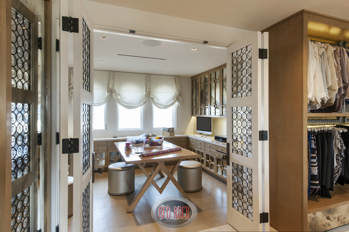 This home includes a spacious home office with a large wood table in the center of the room that includes built-in desks and storage.