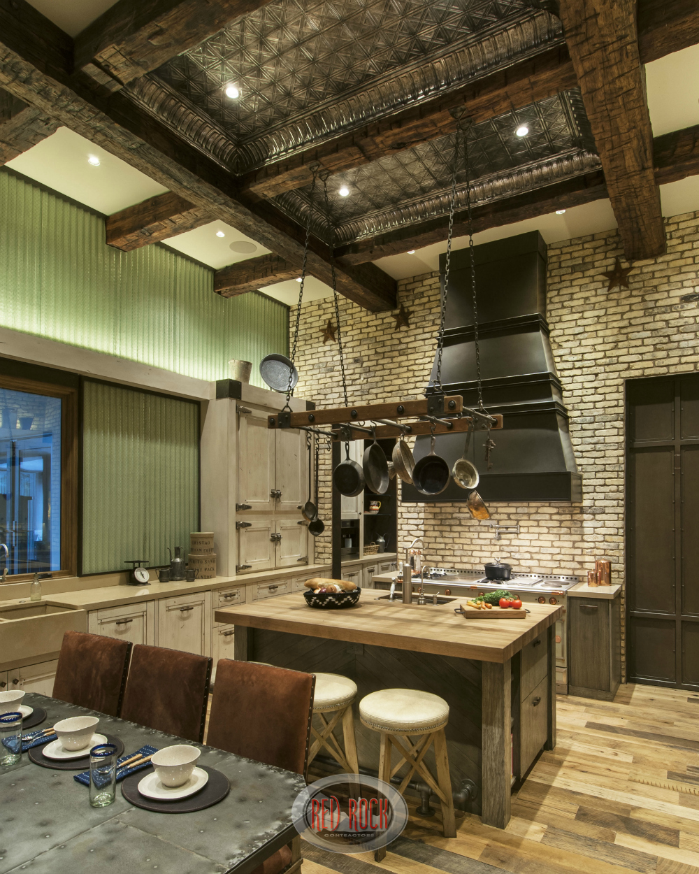 This picture of this custom rustic kitchen shows off the impressive tin and exposed wood elevated ceiling.