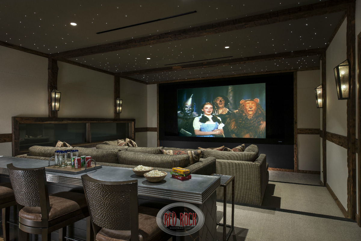 """This is the two tiered home entertainment room with a custom """"space-like"""" ceiling, two massive sofas situated in a stadium seating 2-tiered design. The rear of the room includes a long bar/counter."""