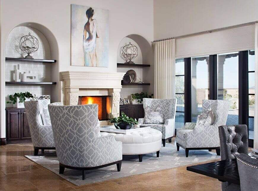 White and grey feature throughout this high ceiling living room, with four high back chairs pivoting around immense white leather circular ottoman.