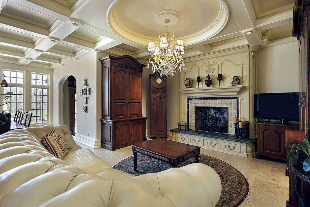 Luxurious textures abound in this living room, from the detailed ceiling pattern to carved wood and tile fireplace surround, full height dark wood cabinetry and grandfather clock, to thick padded white leather sofa.