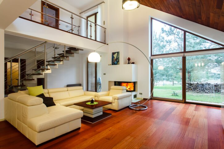 Here's another living room with a sloped hardwood ceiling over natural wood flooring. Catwalk overlooks modern leather sectional wrapping around intricate coffee table with glass shelving. Corner fireplace embedded in white wall between expanses of glass.