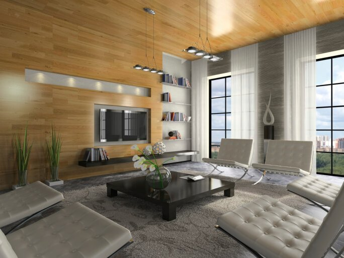 This extra tall living room contrasts grey appointments - including leather seating, area rug, and marble flooring - with light natural hardwood on wall and ceiling. Built-in shelving, full height windows, and hung modern lamps complete the look.