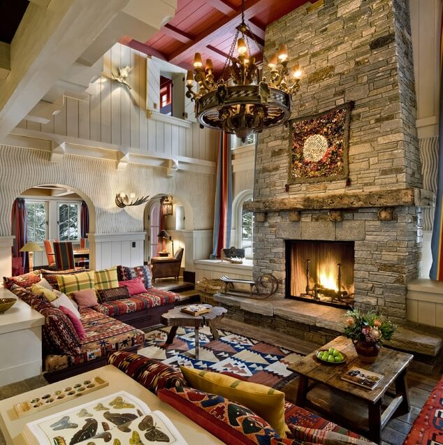 Ultra luxurious rustic styled living room features massive two story stone fireplace in an area packed with details. Southwest patterned rug and sofa coverings contrast with simply white carved wood walls all around, with exposed beams on the red ceiling hanging above ornate wood chandelier.