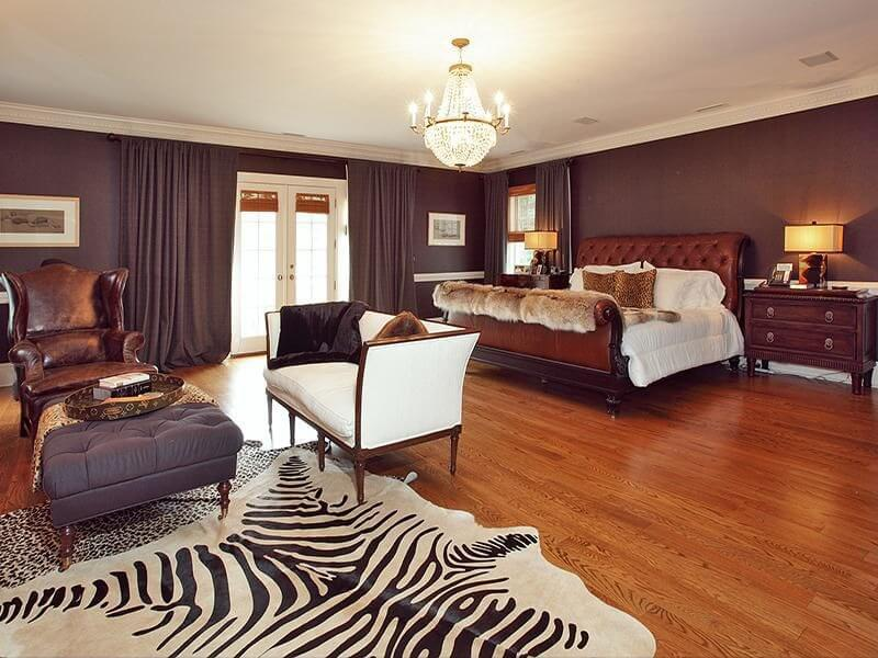 This spacious bedroom incorporates zebra print with an area rug adjacent to the sitting area. There are other animal print items in the room, so the zebra rug works well.