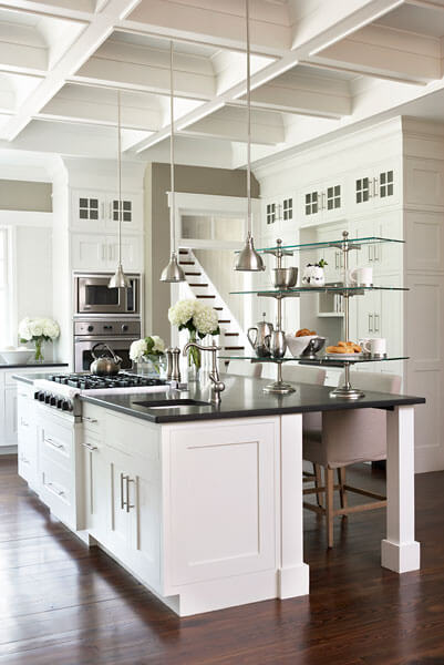 The kitchen features a sprawling island in white with black countertop, featuring built-in range, sink, and space for seating. Stainless steel and glass standalone shelving sits on countertop.