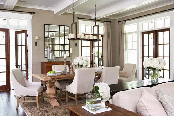 Elaborately detailed living room spikes the dominant neutral tones with rich natural wood in a variety of shades, including large carved dining table. Natural wood French doors with white window frames circle the space.