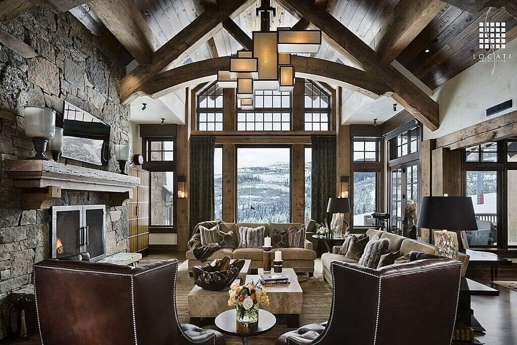 Soaring, vaulted ceiling with exposed natural wood beams frame this luxurious, rustic living room. Large, multi-part cofee table stands before full height stone fireplace, with open views to the mountainside through floor to ceiling glass.