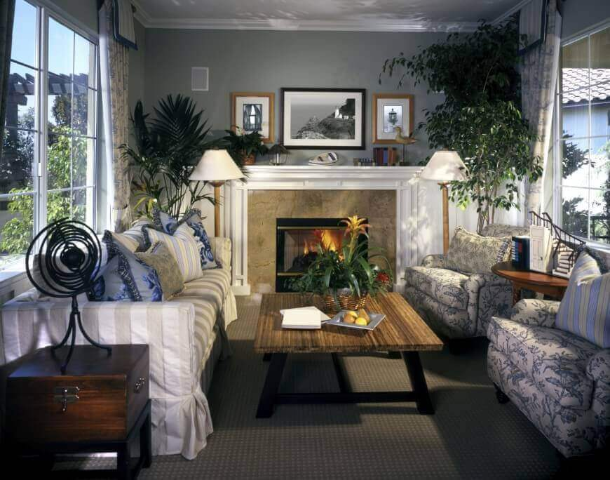 Cozy living room with lavish touches: marble and white wood fireplace surround, lush wood coffee table, thick cushioned seating, and large windows on both sides for natural lighting.