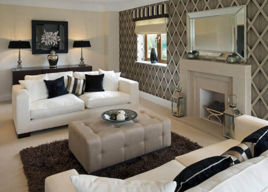 Modern look living room features white sofas with dark decorative pillows facing over rectangular grey ottoman. Detailed wall patterns wrap around marble fireplace.