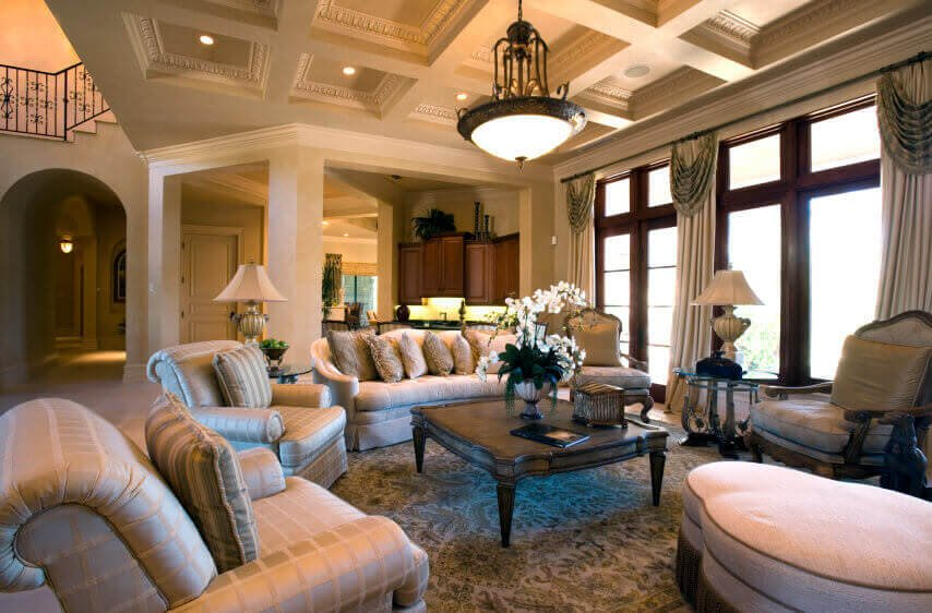 Luxurious open space living room holds this area surrounded in patterned, thick cushion furniture, centering on large carved wood coffee table beneath dome chandelier.