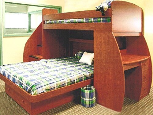 This twin over full L-shaped bunk bed is constructed of engineered wood which helps prevent warping. One side is a desk with drawers while the other side is a staircase to the upper bunk. There's an open bookshelf on the headboard of the lower bed.