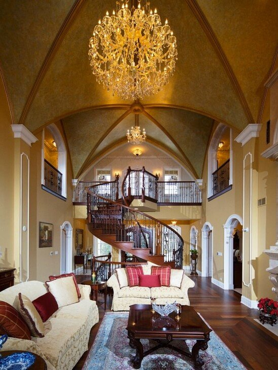 Grand, central living room in yellow and white, with dark hardwood flooring and spiral staircase, stands below curved vaulted ceiling and balcony overlooks. Dark wood furniture and white patterned sofas fill out the space.