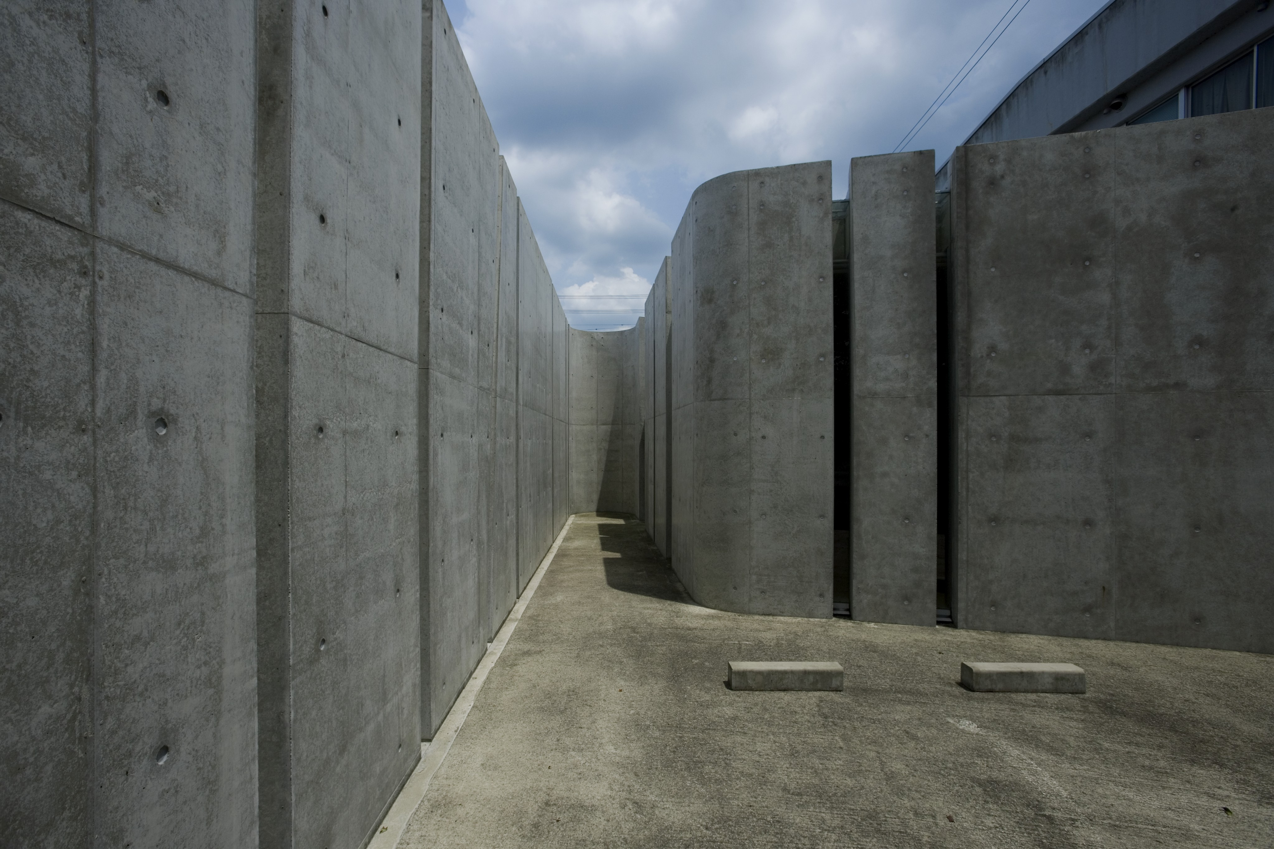 The curved, monolithic appearance of the walls are neatly broken up by both vertical and angled slits.