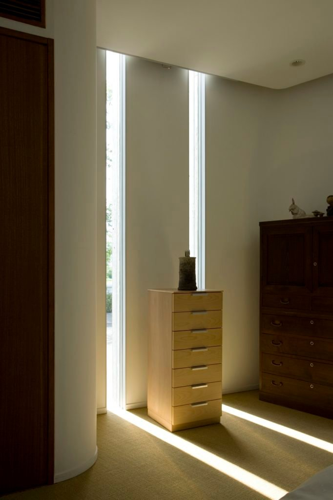 The minimalist decor pairs well with the home itself. Here we see dark wood dresser and lighter, smaller wood dresser flanked by two slits, pouring sunlight into the home.