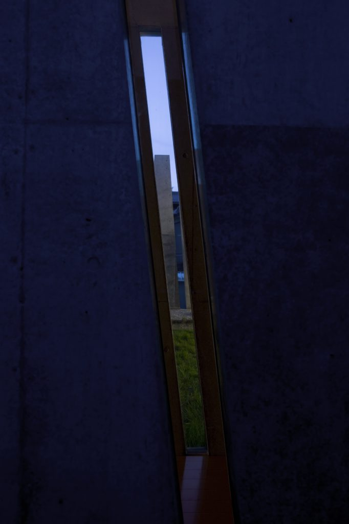 One final glance through an exterior slit toward the yard and beyond.