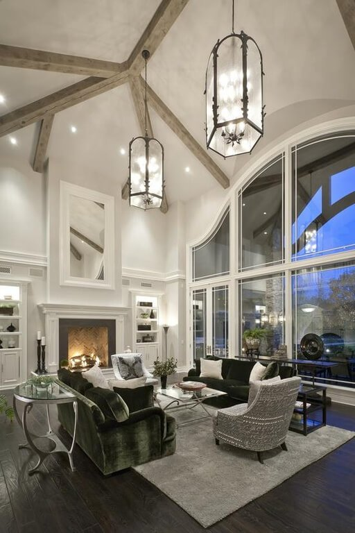High contrast living room pairs black hardwood flooring with white walls, reaching up to a vaulted ceiling with exposed natural wood beams. Immense arched two-story windows define the view, with set of green and grey furniture pieces on grey rug wrapped around metal and glass tables.