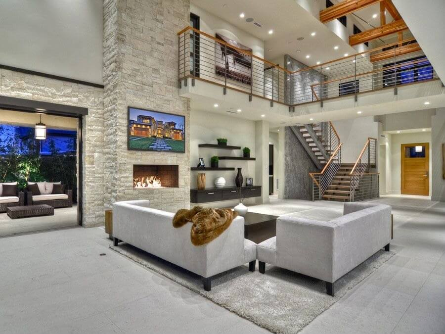 Acute mixture of grey neutral tones mixed with natural wood in this immense living room. Grey tile flooring and matching sofa set stand before full height stone fireplace, while wood railing catwalk hangs overhead.