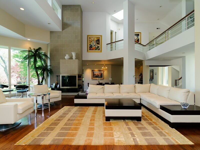 Modern styled living room includes angular upper level catwalk overlooking an expanse of hardwood flooring, with massive L-shaped white sectional matching blackt-topped coffee table and white swivel chairs. Fireplace in beige brick stands at rear, next to full height windows.