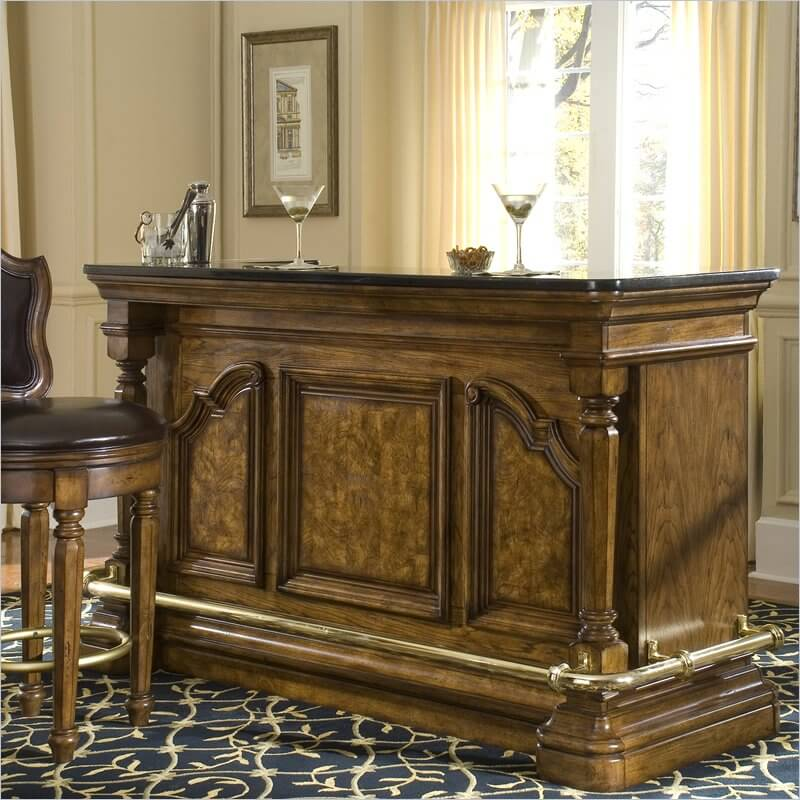 This substantial home bar unit built with hardwood is a luxury unit with ornate woodwork, laminate granite top, brass finished rail, and for safety, offers locking doors.